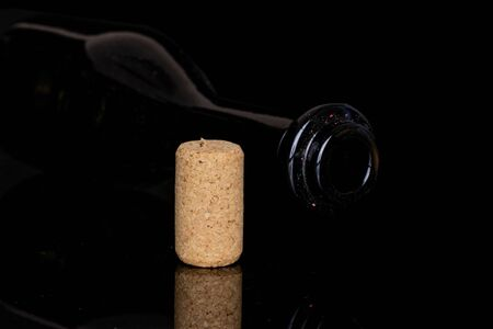 One whole common wine cork  with glass bottle isolated on black glass