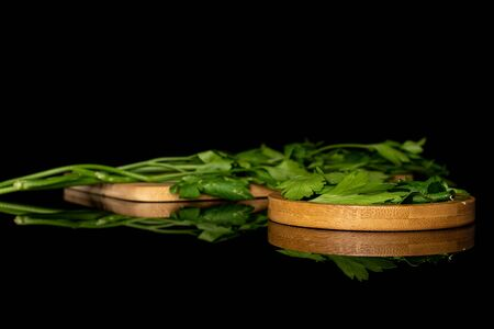 Lot of whole lot of pieces of fresh green parsley on round bamboo coaster on wooden cutting board isolated on black glass