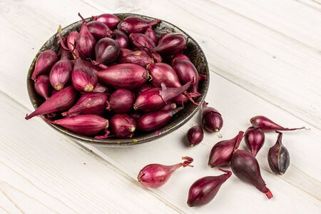 Lot of whole small red onion bulb in dark ceramic bowl on white wood