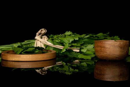 Lot of whole lot of pieces of fresh green parsley on round bamboo coaster in bamboo bowl with straw rope isolated on black glass Banco de Imagens