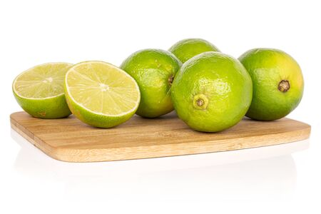 Group of four whole two halves of sour green lime on bamboo cutting board isolated on white background