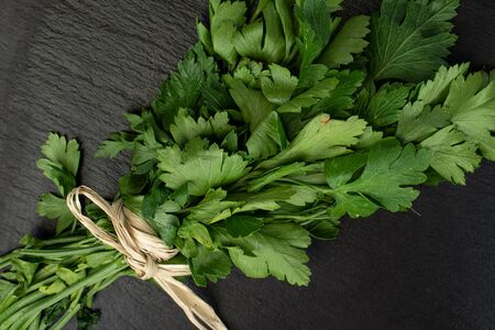 Lot of whole fresh green parsley with straw rope flatlay on grey stone Banco de Imagens