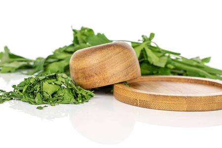 Lot of whole lot of pieces of chopped fresh green parsley on round bamboo coaster in bamboo bowl isolated on white background Banco de Imagens