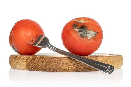 Group of two whole stale red tomato on bamboo plate with metal fork isolated on white background