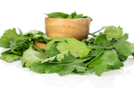 Lot of whole lot of pieces of fresh green parsley leaves on round bamboo coaster in bamboo bowl isolated on white background