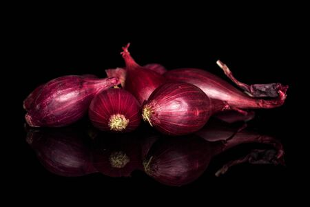 Lot of whole small red onion bulb isolated on black glass