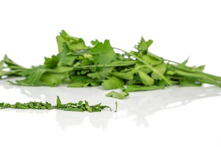 Lot of whole lot of pieces of chopped fresh green parsley isolated on white background