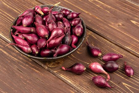 Lot of whole small red onion bulb in dark ceramic bowl on brown wood Reklamní fotografie