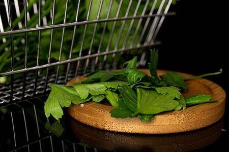 Lot of whole lot of pieces of fresh green parsley leaves on round bamboo coaster on shopping basket isolated on black glass