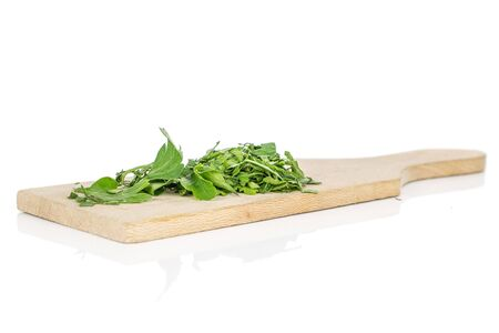 Lot of pieces of fresh green parsley on wooden cutting board isolated on white background