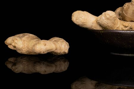 Group of three whole fresh brown ginger in glazed bowl isolated on black glass Reklamní fotografie