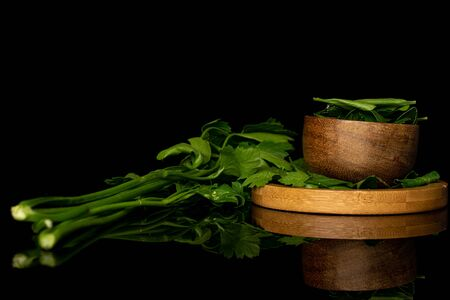 Lot of whole lot of pieces of fresh green parsley on round bamboo coaster in bamboo bowl isolated on black glass