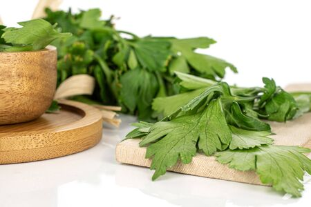Lot of whole lot of pieces of fresh green parsley on round bamboo coaster in bamboo bowl with straw rope isolated on white background