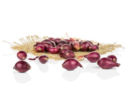 Lot of whole small red onion bulb on natural sackcloth isolated on white background Reklamní fotografie