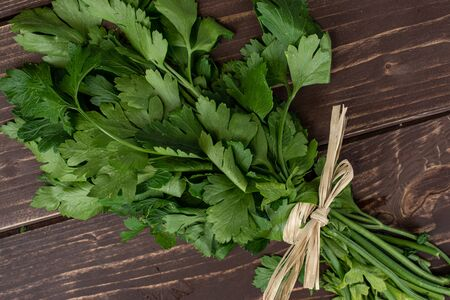 Lot of whole fresh green parsley with straw rope flatlay on brown wood