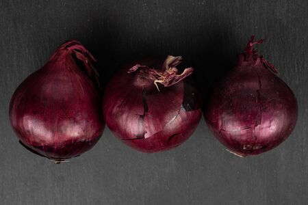 Group of three whole small red onion bulb flatlay on grey stone