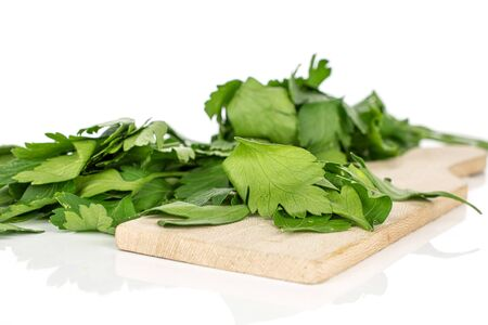 Lot of whole fresh green parsley on wooden cutting board isolated on white background