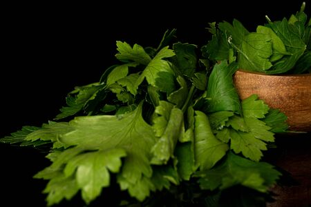 Lot of whole lot of pieces of fresh green parsley in bamboo bowl isolated on black glass