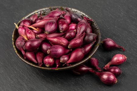 Lot of whole small red onion bulb in dark ceramic bowl on grey stone