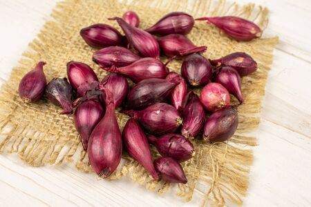 Lot of whole small red onion bulb on natural sackcloth on white wood