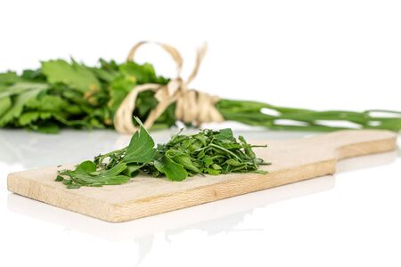Lot of whole lot of pieces of fresh green parsley on wooden cutting board with straw rope isolated on white background Banco de Imagens