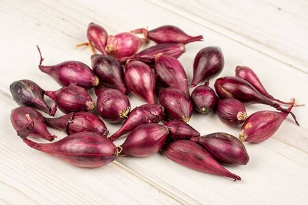 Lot of whole small red onion bulb on white wood