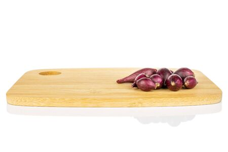 Lot of whole small red onion bulb on bamboo cutting board isolated on white background