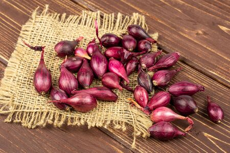 Lot of whole small red onion bulb on natural sackcloth on brown wood Reklamní fotografie