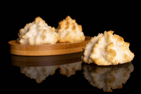 Group of three whole homemade golden coconut biscuit on bamboo coaster isolated on black glass Stock Photo