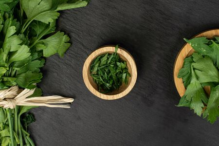 Lot of whole lot of pieces of fresh green parsley with straw rope on round bamboo coaster in bamboo bowl flatlay on grey stone