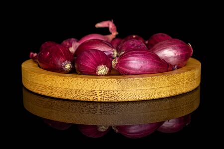 Lot of whole small red onion bulb on bamboo coaster isolated on black glass