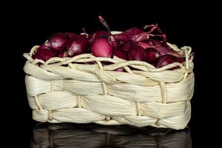 Lot of whole small red onion bulb in bast basket isolated on black glass