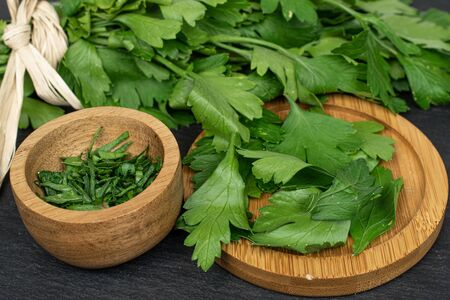Lot of whole lot of pieces of fresh green parsley with straw rope on round bamboo coaster in bamboo bowl on grey stone Banco de Imagens