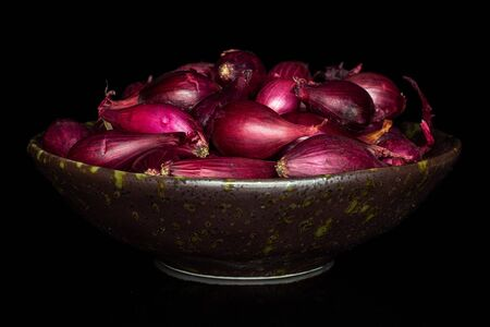 Lot of whole small red onion bulb in dark ceramic bowl isolated on black glass