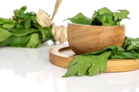 Lot of whole lot of pieces of fresh green parsley front focus on round bamboo coaster in bamboo bowl isolated on white background