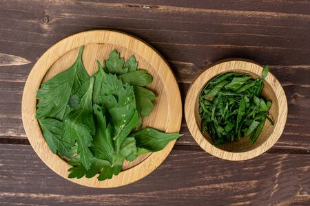 Lot of whole lot of pieces of fresh green parsley leaves on round bamboo coaster in bamboo bowl flatlay on brown wood