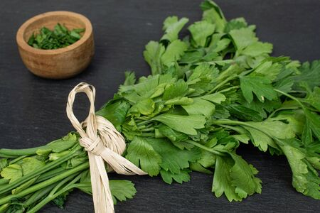 Lot of whole lot of pieces of fresh green parsley with straw rope in bamboo bowl on grey stone