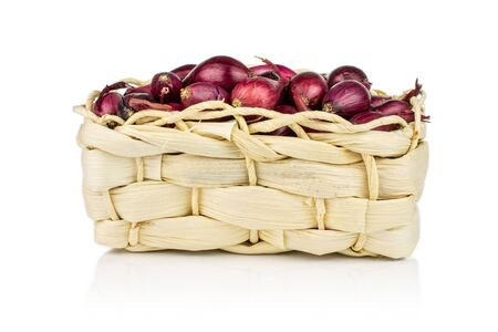 Lot of whole small red onion bulb in bast basket isolated on white background