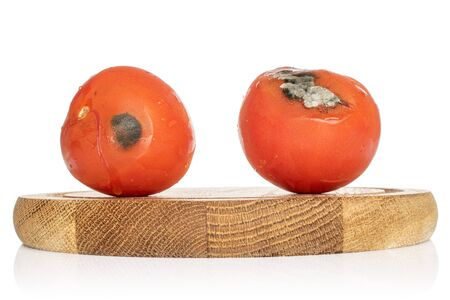 Group of two whole stale red tomato on bamboo plate isolated on white background Zdjęcie Seryjne