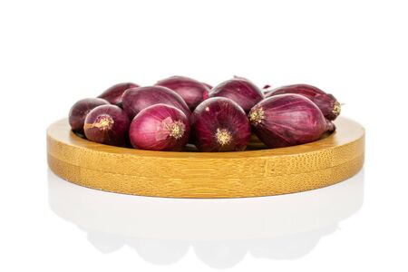 Lot of whole small red onion bulb on bamboo coaster isolated on white background