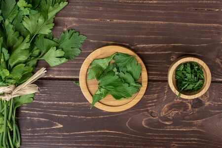 Lot of whole lot of pieces of fresh green parsley on round bamboo coaster in bamboo bowl with straw rope flatlay on brown wood Banco de Imagens