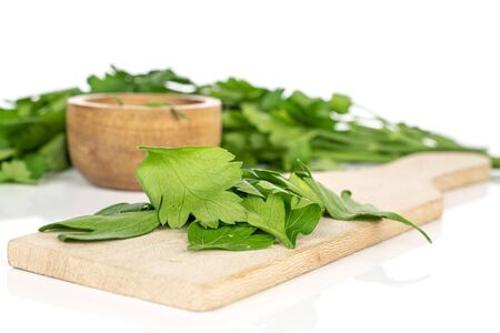 Lot of whole lot of pieces of fresh green parsley in bamboo bowl on wooden cutting board isolated on white background