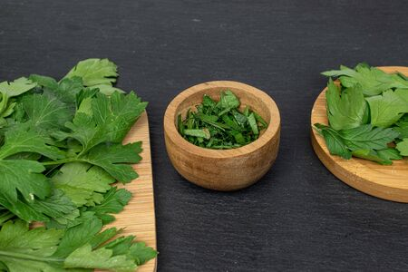 Lot of whole lot of pieces of fresh green parsley on bamboo cutting board on round bamboo coaster in bamboo bowl on grey stone