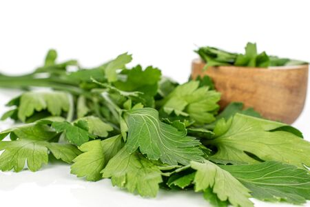 Lot of whole lot of pieces of fresh green parsley in bamboo bowl isolated on white background