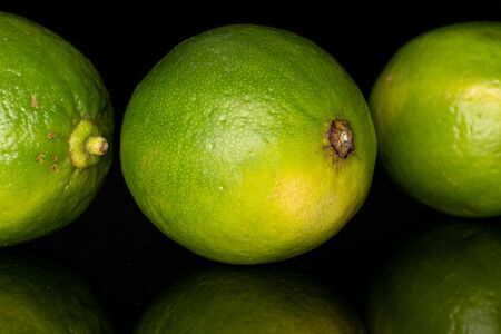 Group of three whole sour green lime isolated on black glass