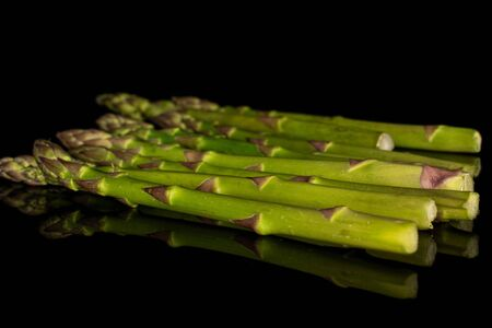 Lot of whole arranged healthy green asparagus isolated on black glass