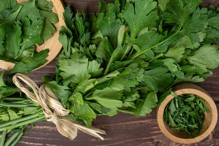 Lot of whole lot of pieces of fresh green parsley leaves on round bamboo coaster in bamboo bowl with straw rope flatlay on brown wood
