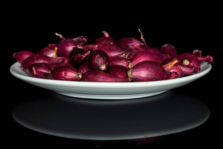 Lot of whole small red onion bulb on white ceramic plate isolated on black glass
