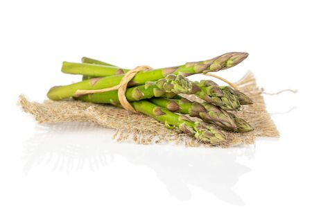 Lot of whole healthy green asparagus with straw rope and jute fabric isolated on white background