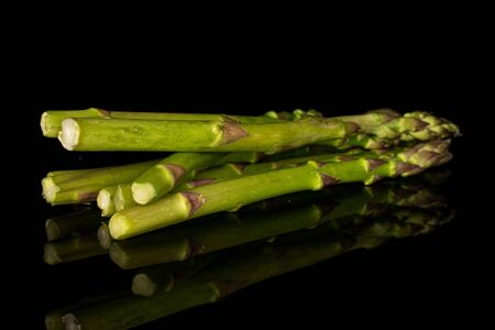 Group of six whole healthy green asparagus isolated on black glass